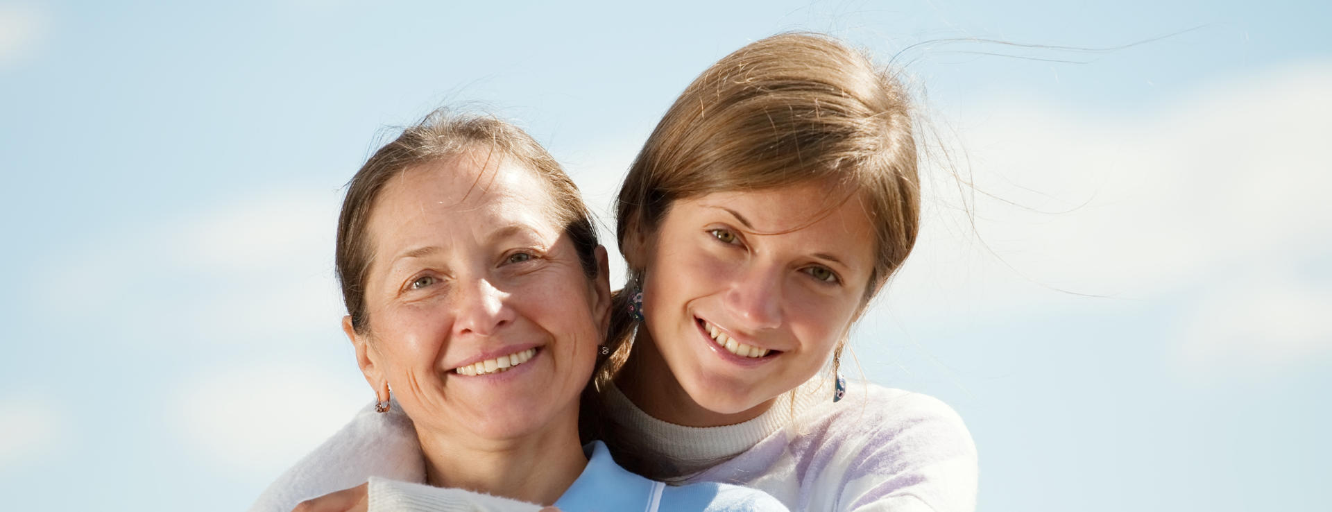 Portrait of mother with teen daughter against sky
